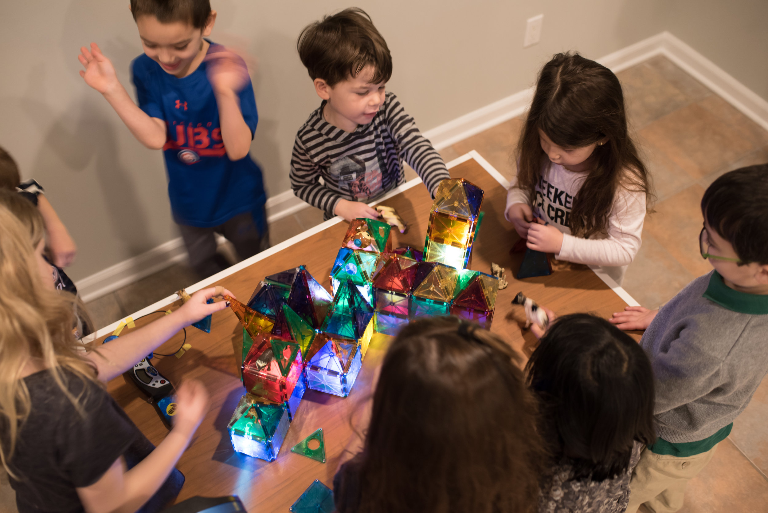 Children building an illuminated magnetic tile city.