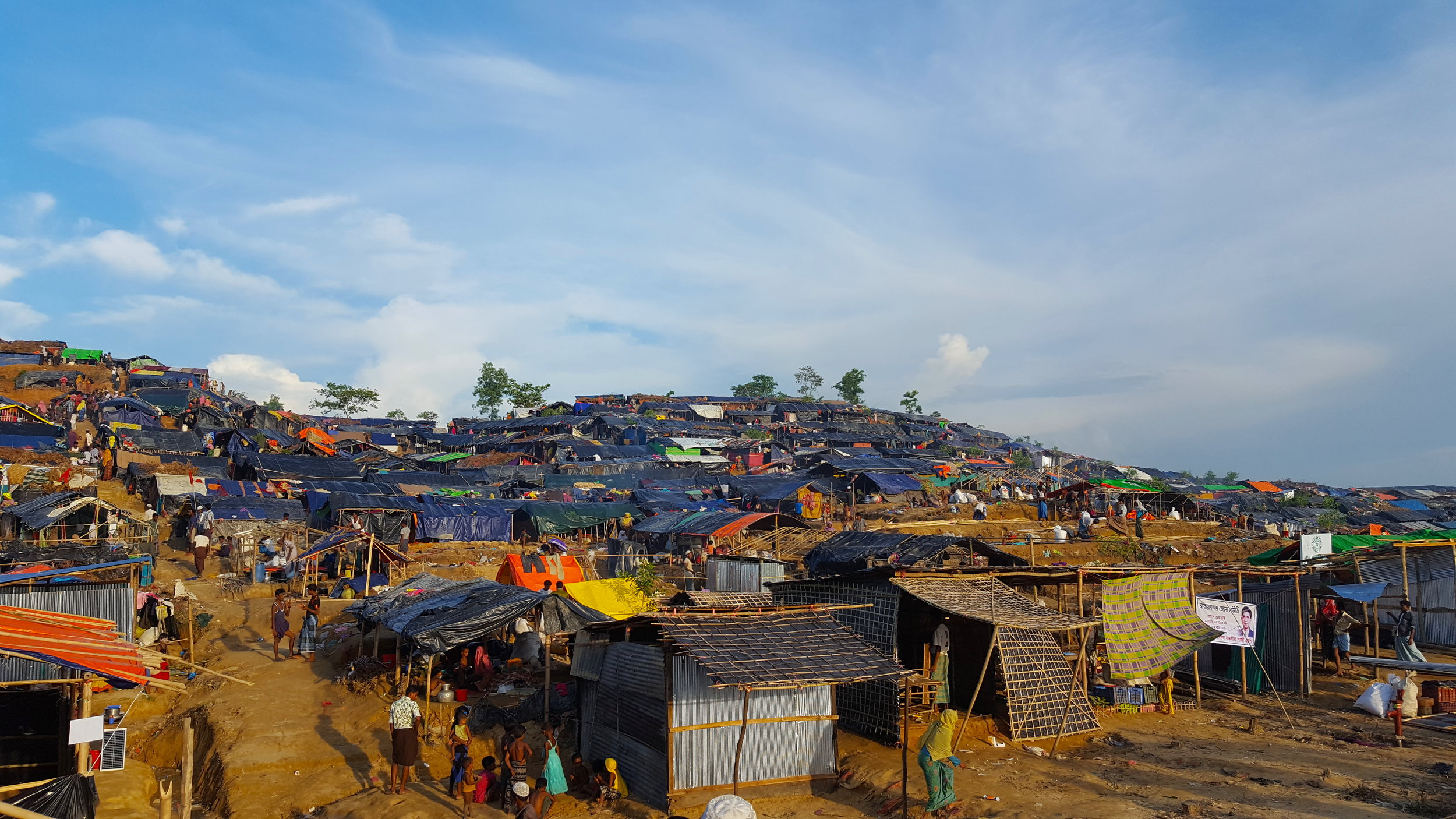 There are two main types of Rohingya refugee camps: makeshift camps and government-operated camps recognized by the Bangladeshi state. The former frequently spring out of the latter, though it is difficult to tell where one ends and the other begins, as refugees frequently set up new camps adjacent to existing ones. Since the upsurge in violence against the Rohingya in August 2017, the makeshift Kutupalong camp and surrounding camps at Ghumdum, Balukhali, and Thangkhali have swelled rapidly and merged into one another. The International Organisation for Migration (IOM) refers to this collective settlement as the Kutupalong-Balukhali expansion site. The pictured favela consists of hundreds of improvised homes that offer little protection from the environment. When it rains, water floods the camps, making it impossible for refugees to sleep on the dirt floors of their dwellings. These homes are equally uninhabitable when it is warm, because the plastic roofing covering most of them absorbs heat very easily.