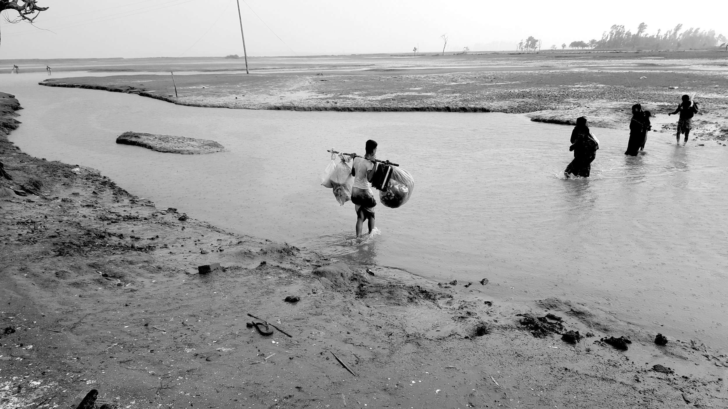 Rohingya carrying their belongings over harsh terrain. Many Rohingya refugees are forced to walk through sites clustered with landmines in order to reach safety. This group crossed the border and arrived on the shores of Bangladesh at 4 am. They are fortunate compared to the nearly four thousand Rohingya stuck at the border of Myanmar.