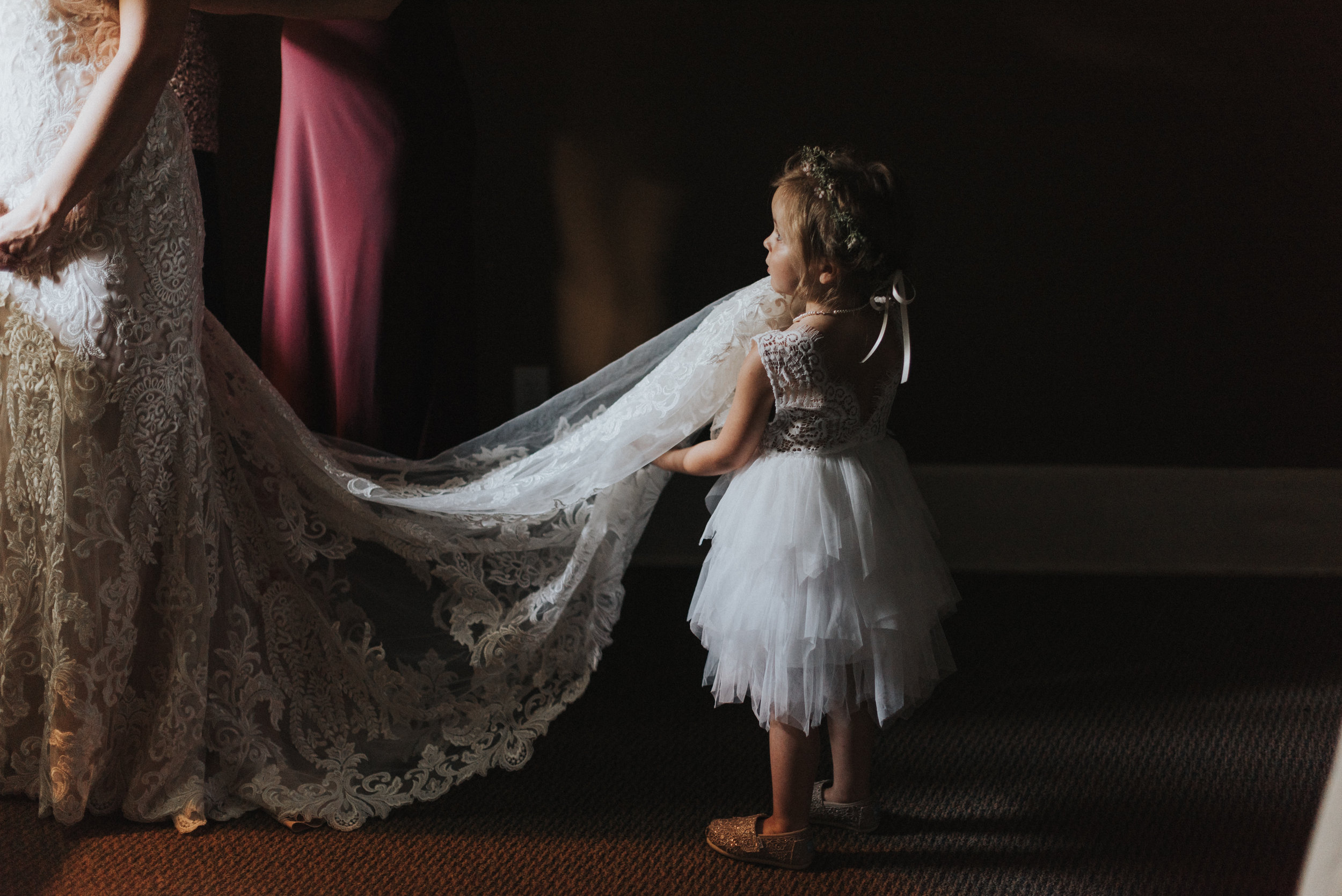 Southern Fete, Southern Wedding, Flower girl posing while holding Bride's dress
