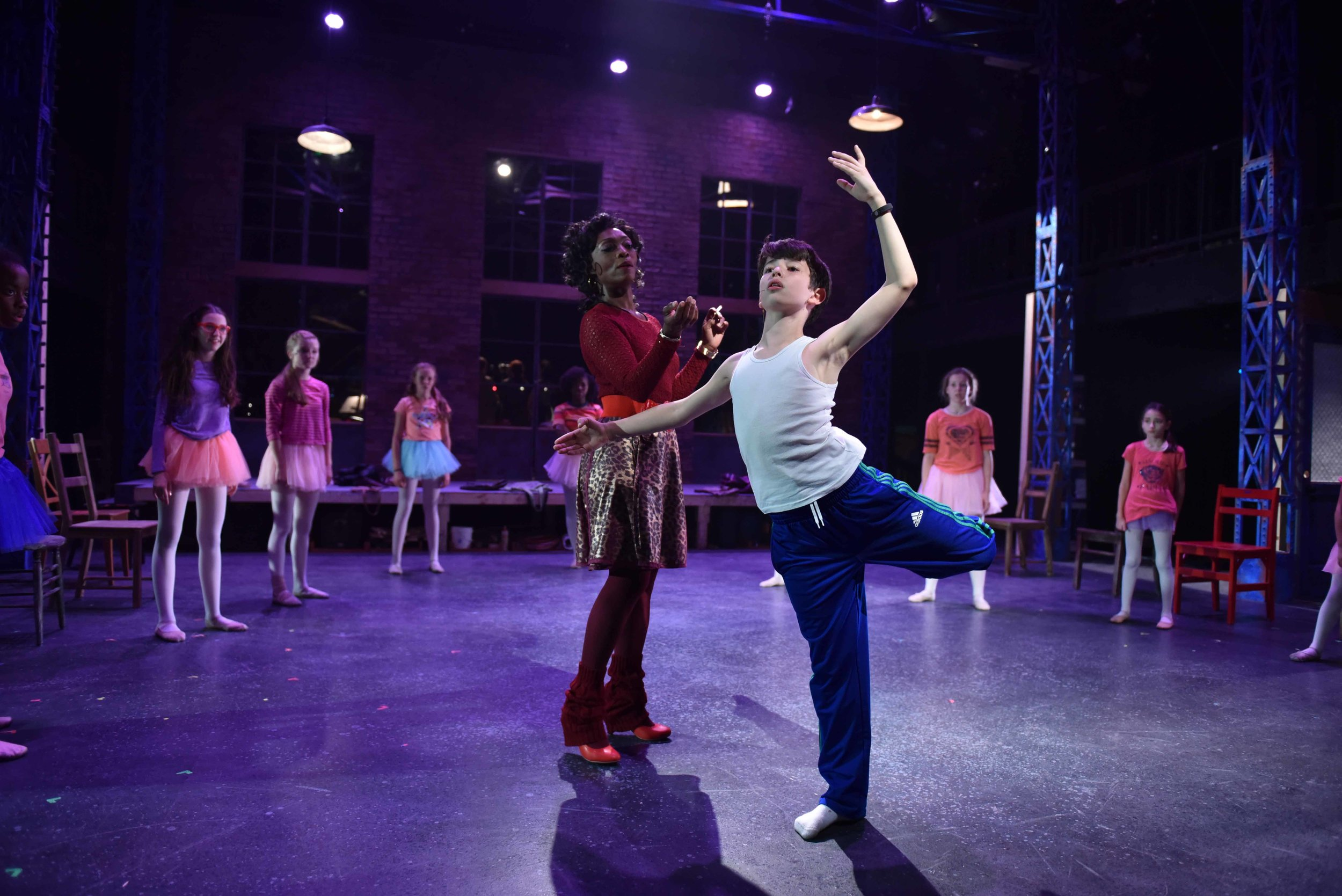 """Shanésia Davis as """"Mrs. Wilkinson,"""" Jacob Kaiser as """"Billy Elliot"""" and ensemble in Porchlight Music Theatre's """"Billy Elliot the Musical."""" Photo by Michael Courier"""