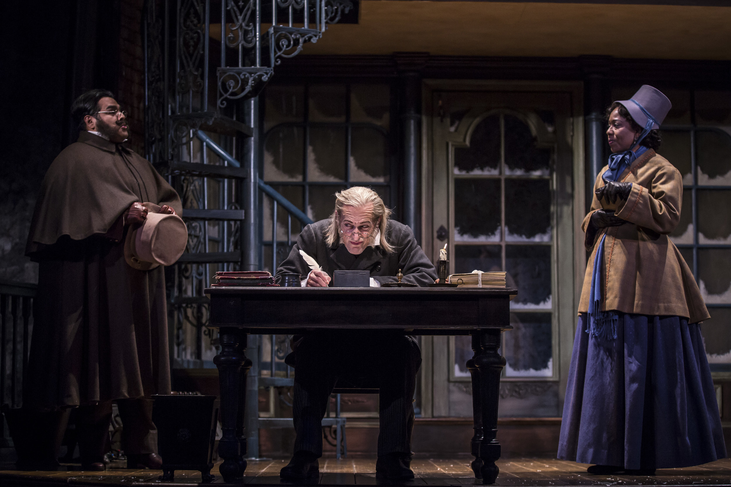 Jonah Winston  (Ortle), Larry Yando  (Ebenezer Scrooge) and  Penelope Walker  (Mrs. Crumb) in the 40th annual production of  A Christmas Carol , directed by Henry Wishcamper.