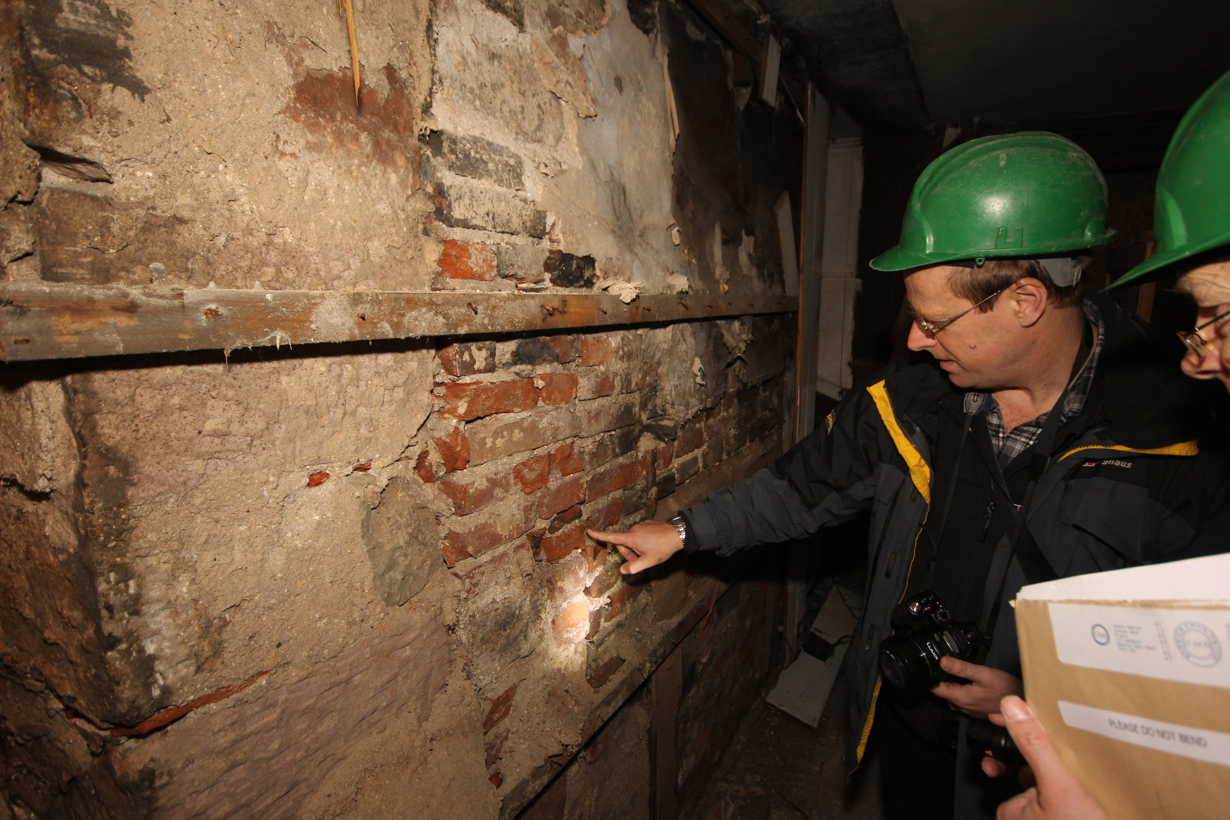 As well as recording, interpretation plays a major part in understanding a building's past. Here, architectural historian Dr Adam Menuge examines a chimney breast in the main shop.