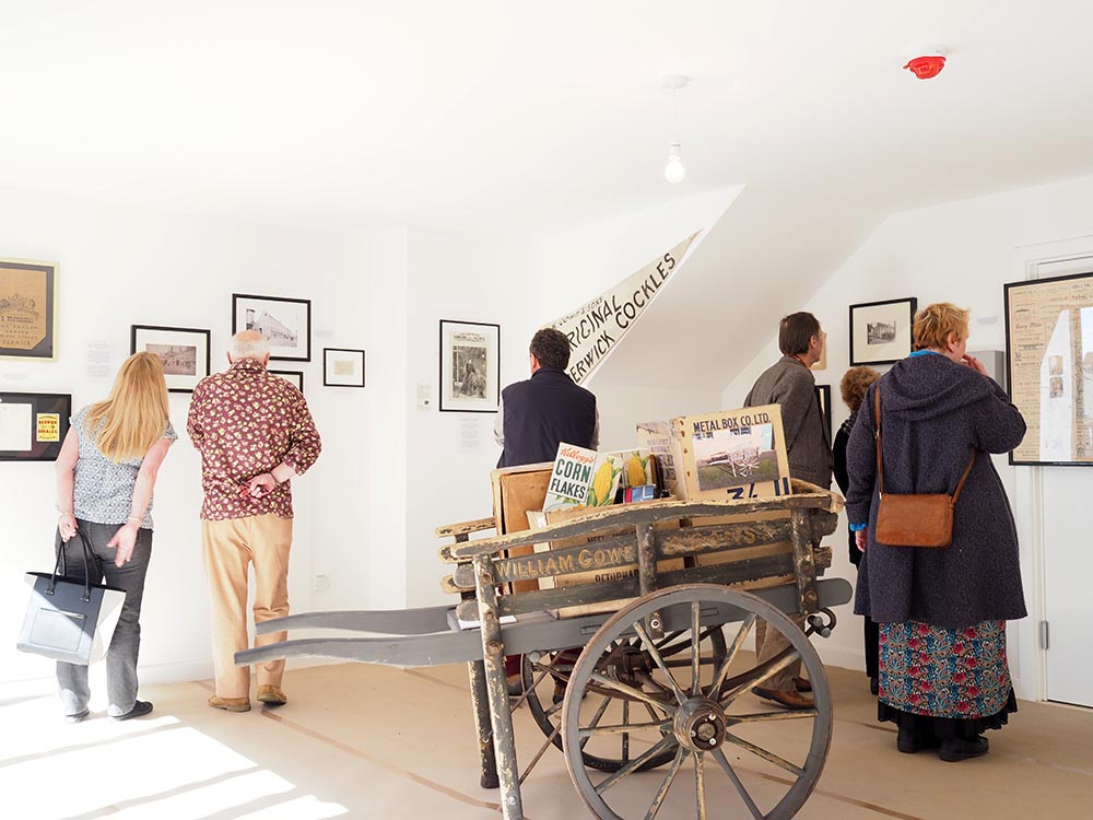 Visitors looking at some of the earlier material in the exhibition, in front, the original shop cart.