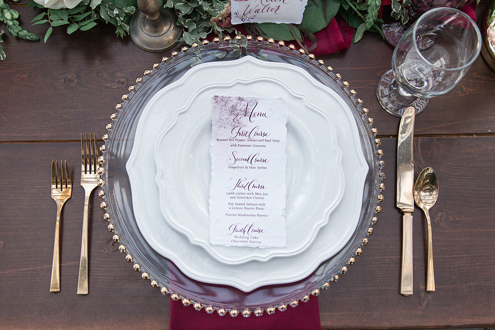 Handmade paper wedding menus create a fine art feel nestled within the antique details of this table design.