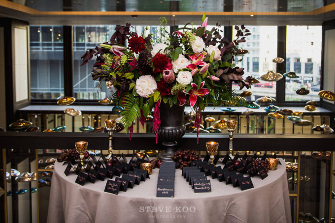 3-langham-wedding-steve-koo-photography-sweetchic-events-vale-of-enna-moody-romantic-wedding-black-escort-cards-tall-arrangement-black-vase-burgundy-wine-white