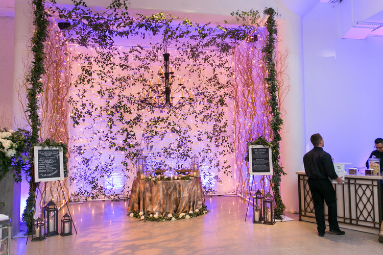 Dramatic ceremony arbor with greenery and curly willow