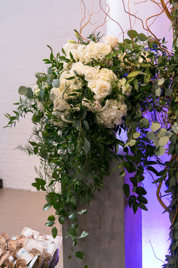 Trailing greenery and white flower ceremony arrangement in an urn