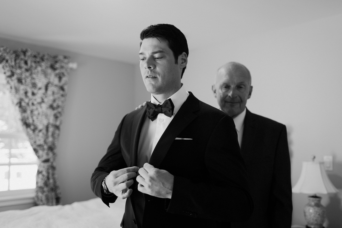 Father of bride helping Adam with his jacket.