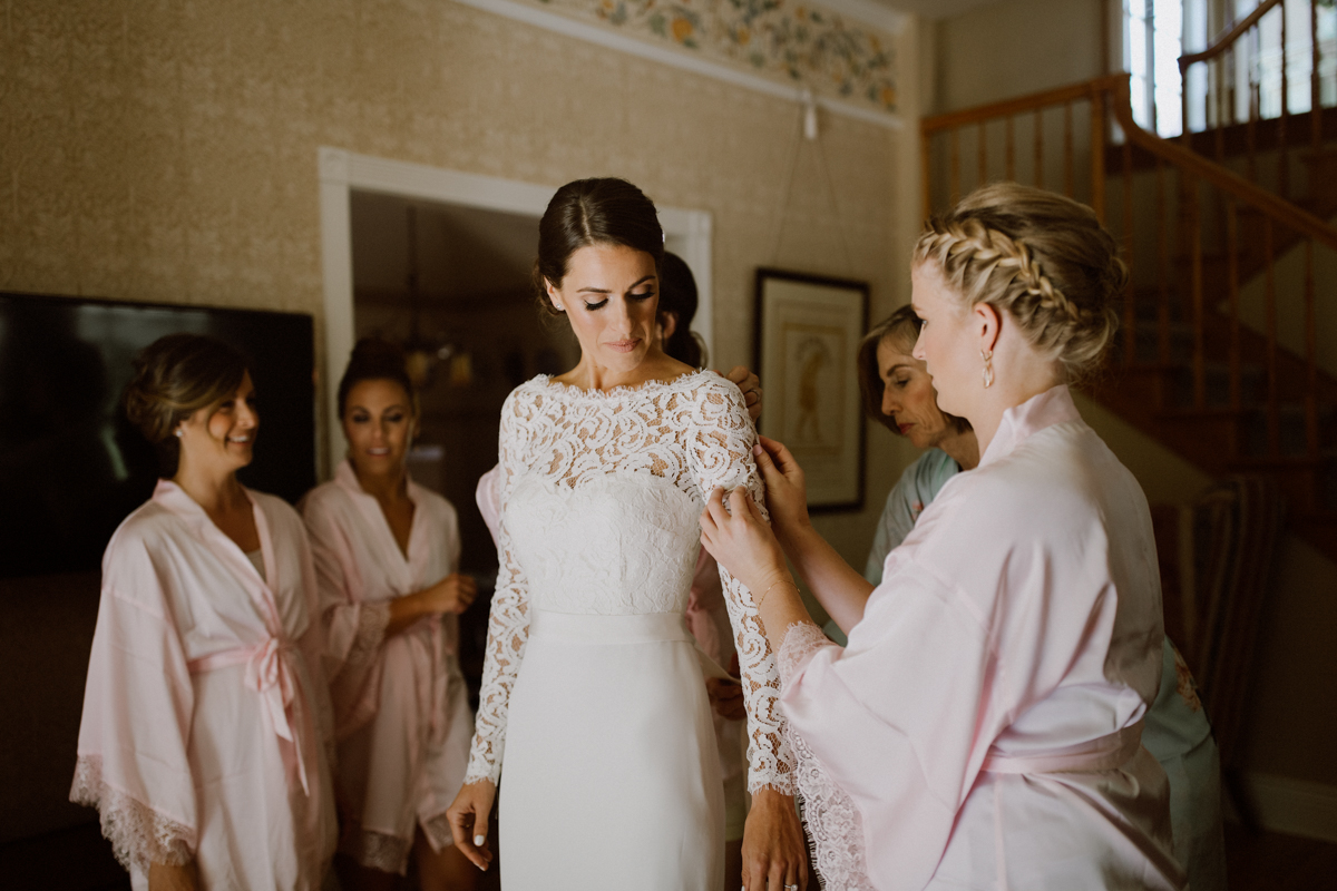 Betsy in her wedding dress surrounded by her bridesmaids.