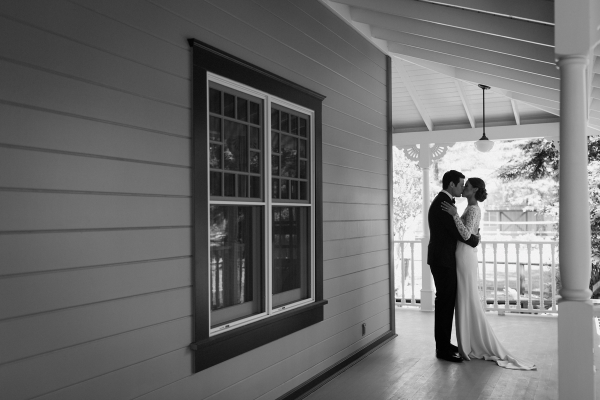 Wide shot of Adam & Betsy kissing on the front porch.
