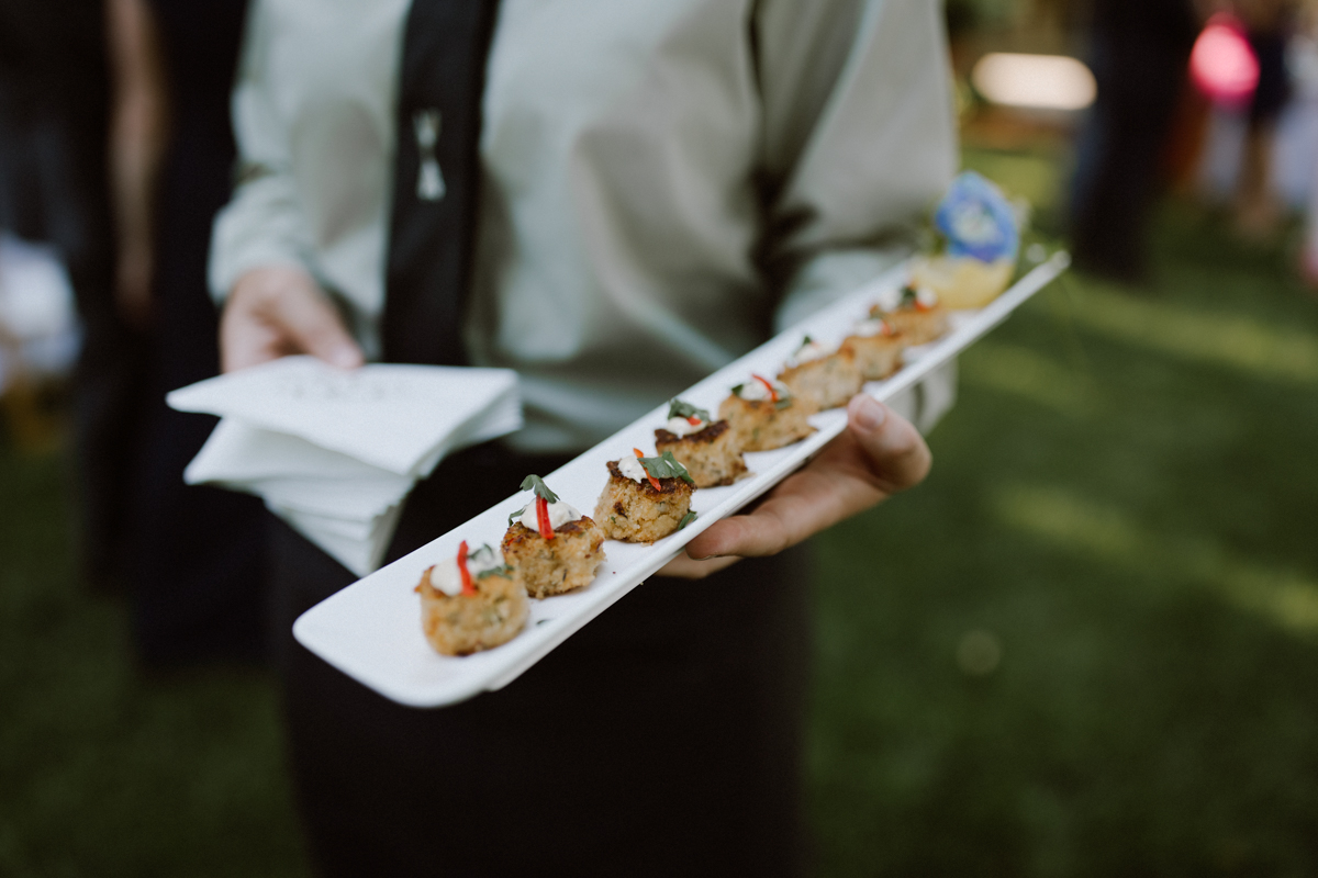 Crab cakes being served at cocktail hour.