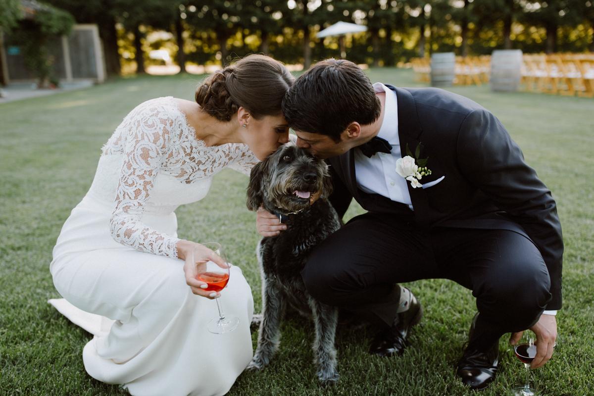 Adam & Betsy kissing their family dog.