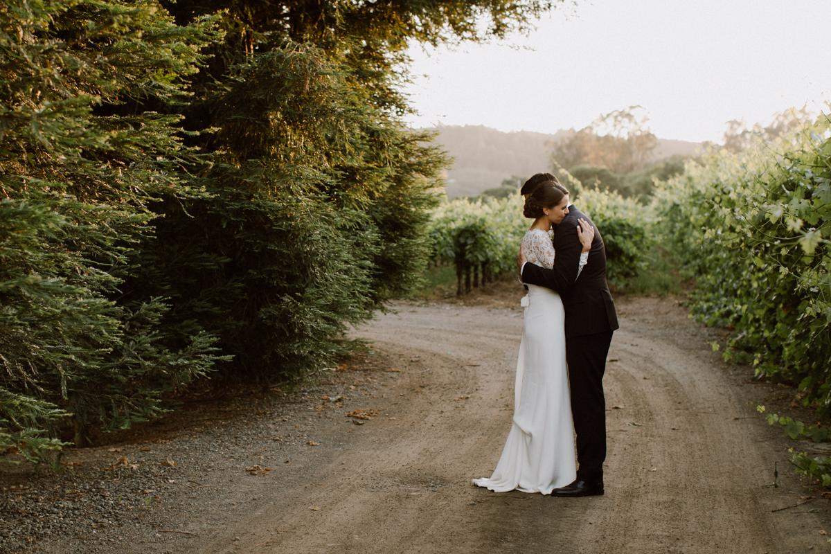 Adam & Betsy hugging on a dirt road.