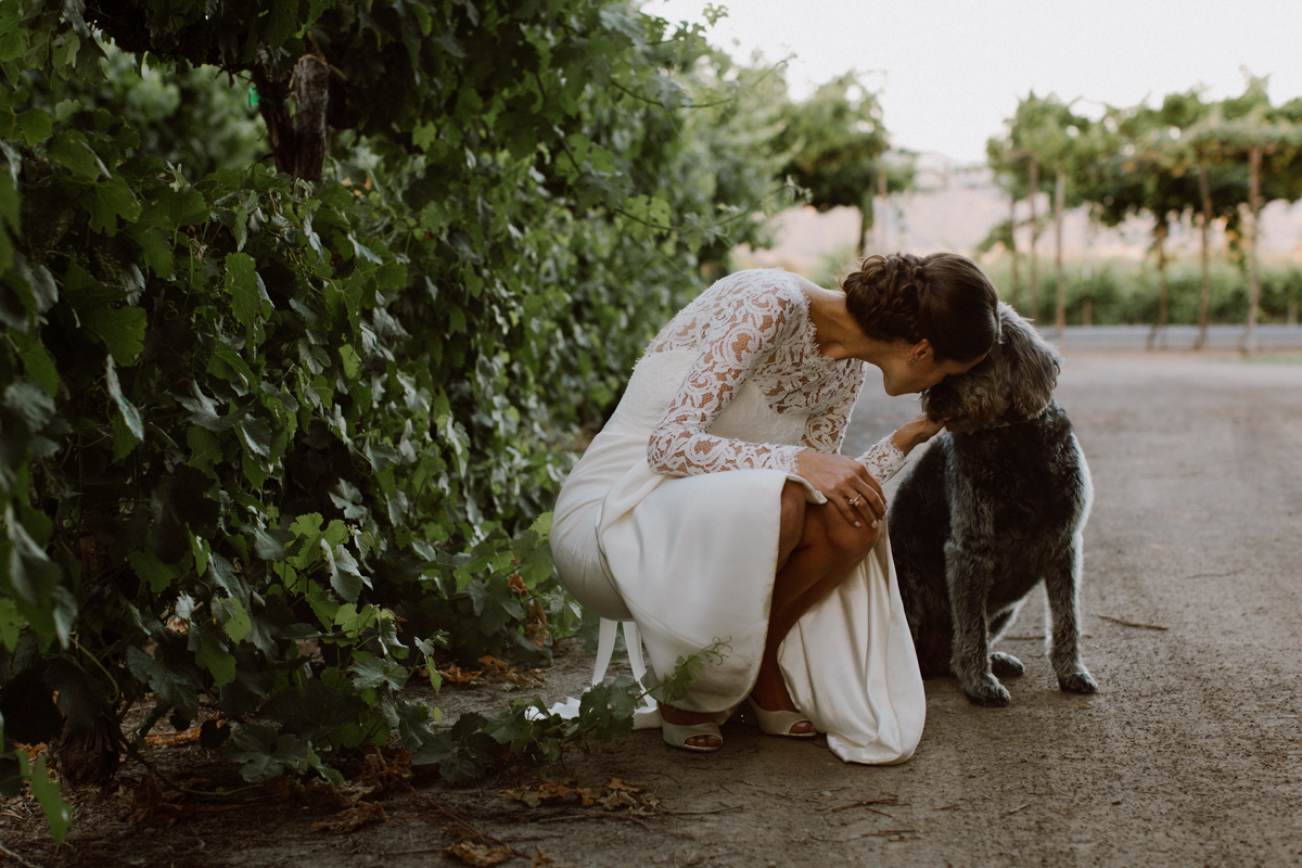 Betsy kissing her family dog in the vineyards.