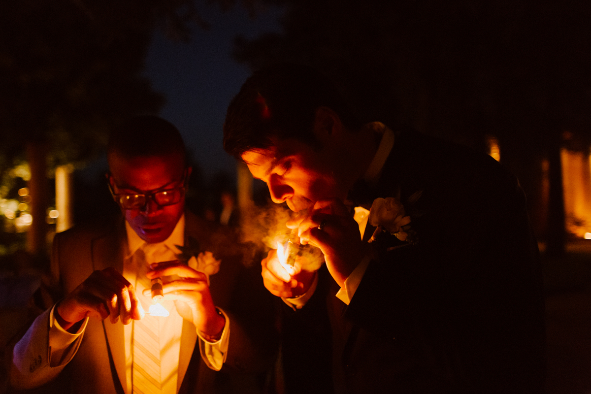 Adam & his best friend lighting a cigar.
