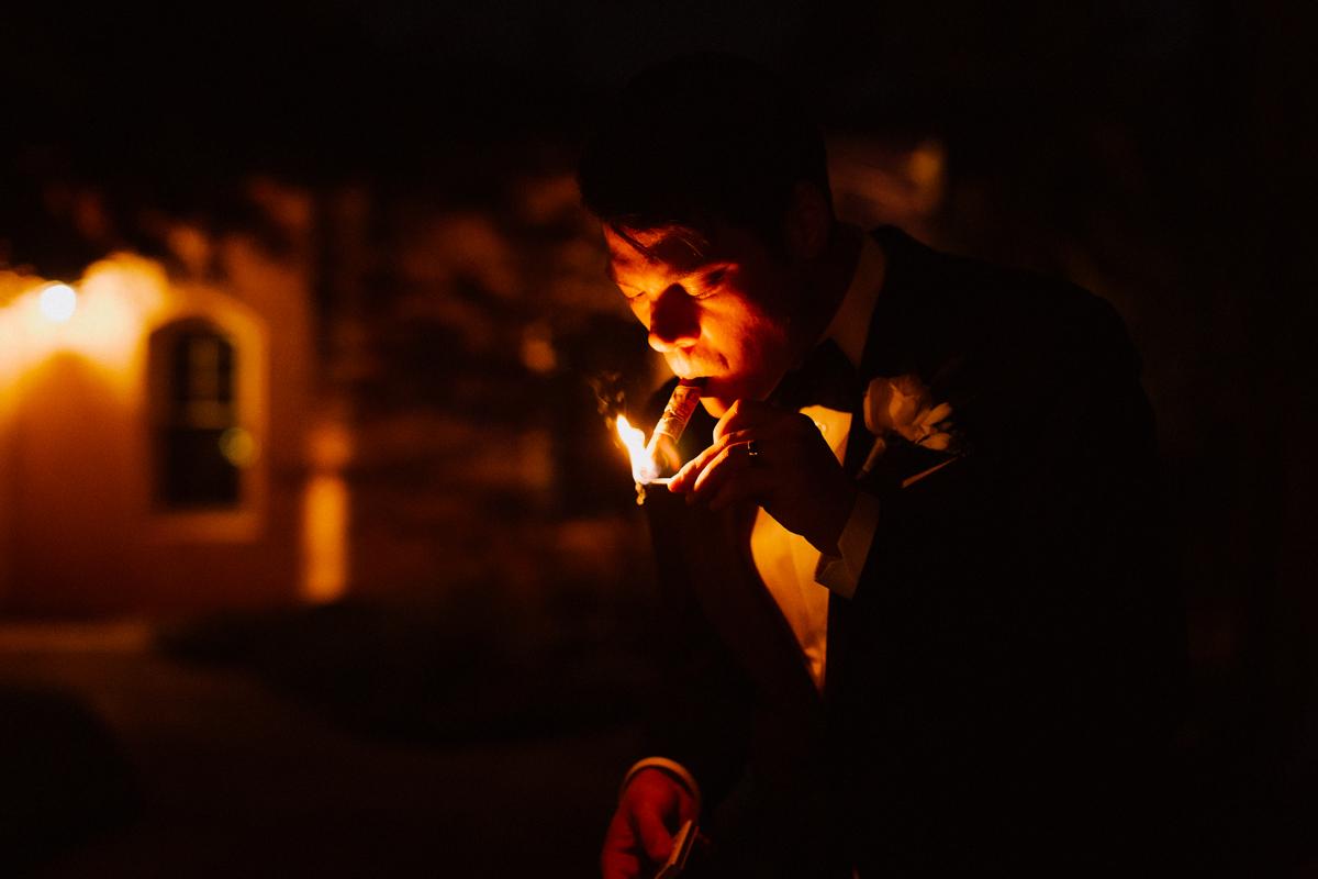 Adam lighting a cigar with a matchstick.