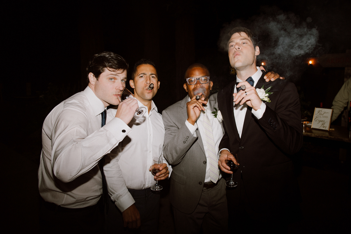 Adam & wedding guest puffing on cigars.