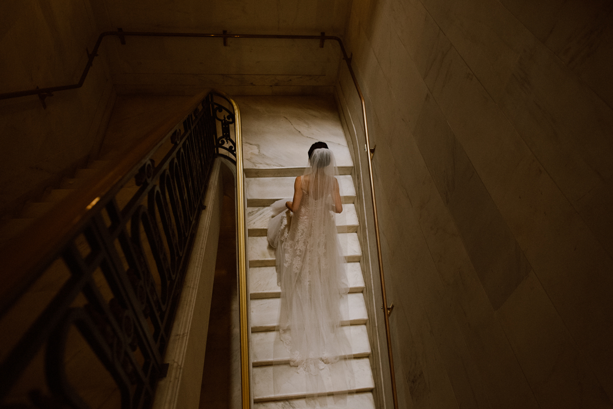 Bride walking up the steps at SF City Hall.