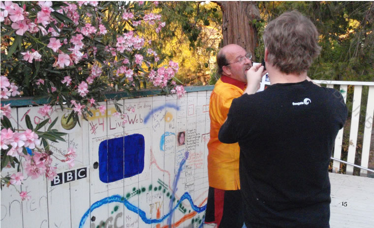 """Robert Scoble interviewing Marc Canter in front of his """"Open Mesh"""" fence mural."""