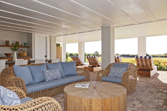 The breezy living room under the house includes an outdoor fireplace and bar, let the weekend begin!