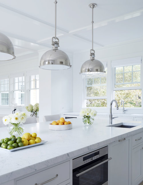 An all white kitchen with large windows to bring in the natural light ...a total dream for any cook!