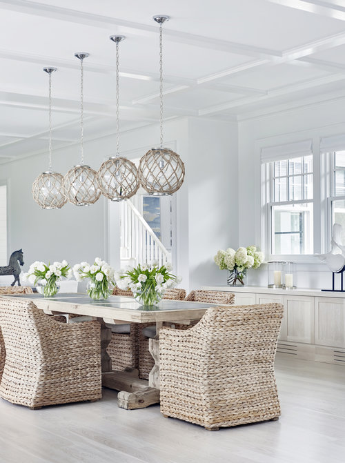 Fresh white walls, bleached oak wide-plank floors give this house a beachy feel, but the steel black windows, coffered ceilings and cool  pendant lighting  gives this beach house an open updated look. The wicker kitchen table and chairs by  Restoration Hardware