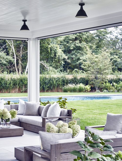 I love the fresh look Hydrangea blooms look in a large glass vase. The driftwood color of this  teak outdoor furniture i s so natural and can be dressed up or down with cushions and pillows
