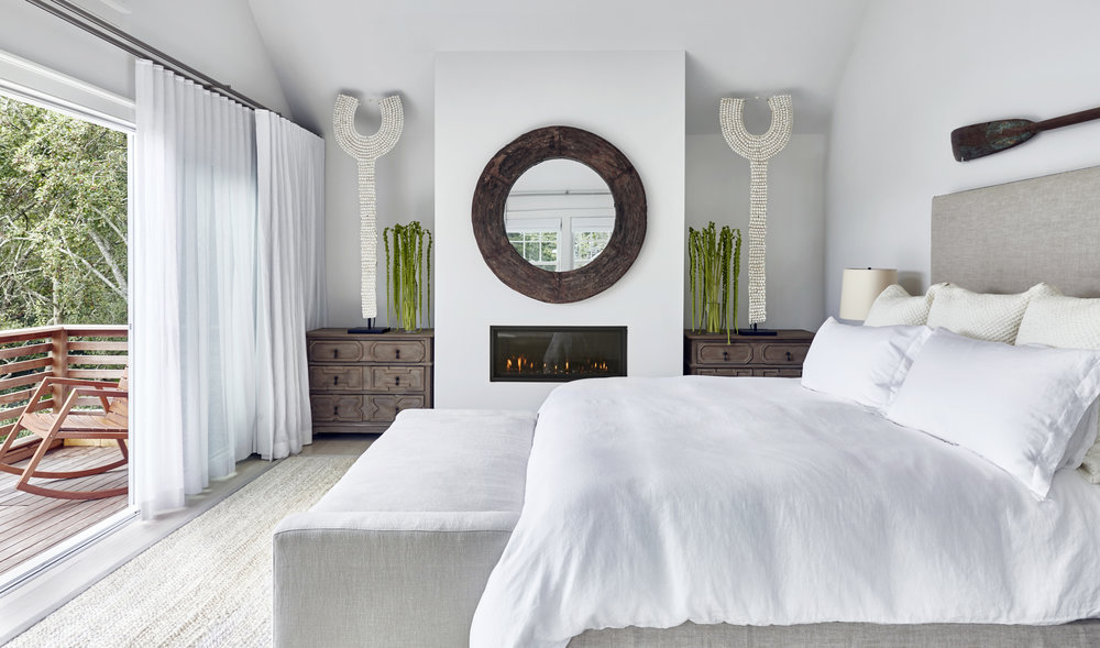 In the master bedroom, an upholstered headboard and bench from   Chango & Co. add warmth via their natural oat color and coolness by virtue of their linen fabric. The round mirror from   Chango & Co. opens up the space and is reminiscent of a porthole. Enjoy the morning sunrise and surf on your own private deck .