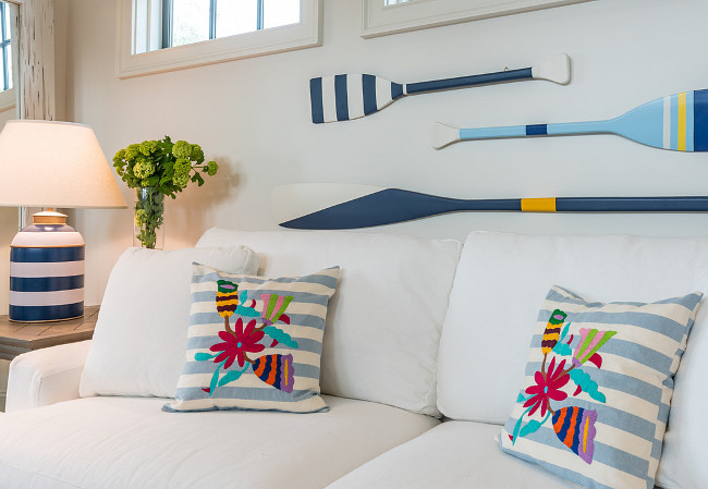 How cute is this room, a couch that pulls out, painted oars, blue and white striped lamp, and bright pillows, this look works for me.  I love the  painted oar decor  and blue and white ceramic  table lamp .