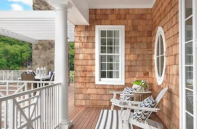 A lovely porch, inviting adirondack chairs to sit in and watch the sun say good night.