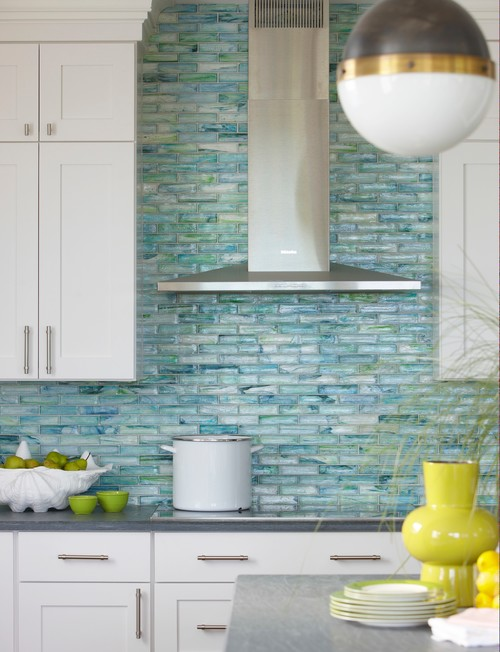 The shimmer of an iridescent tile backsplash calls to mind the glint of sun on crystal-clear water and pearly shells beneath the waves.