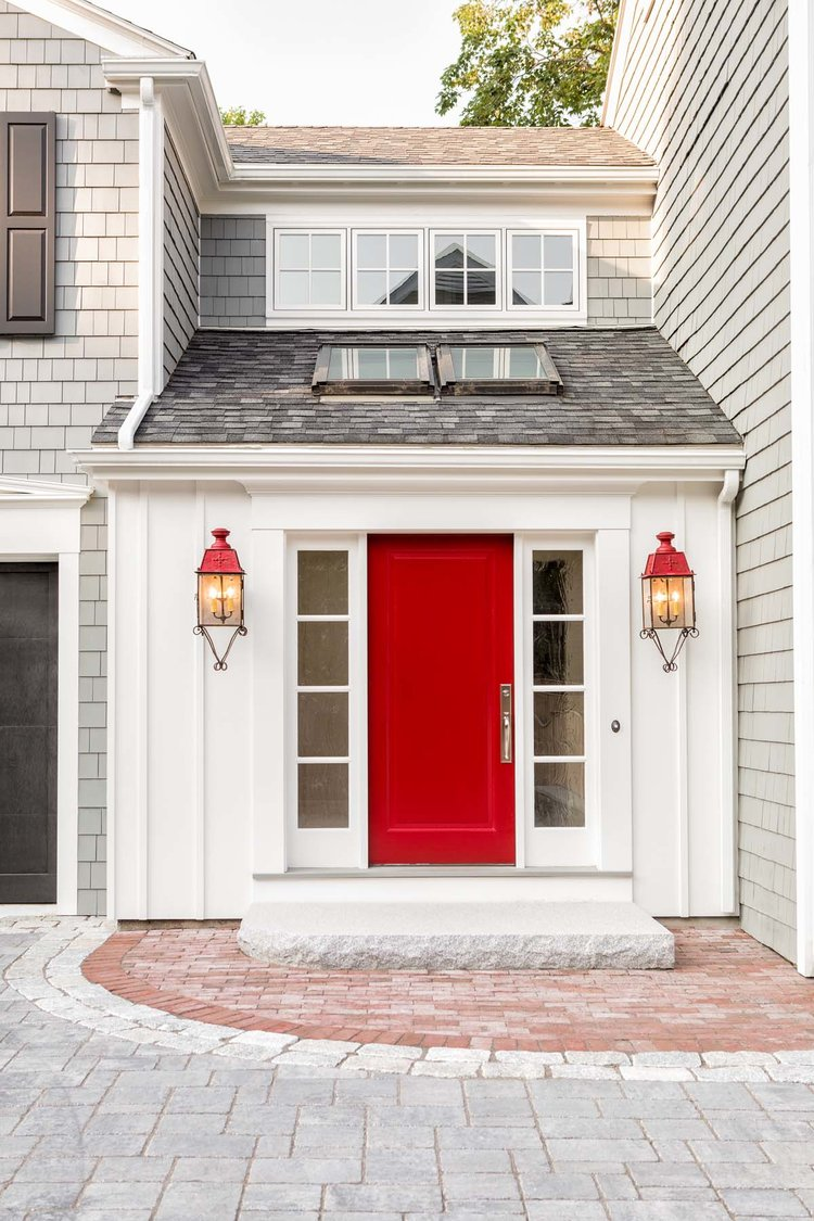 Talk about curb appeal, I love the pretty natural stone front door stoop, the red door and red lighting fixtures add an inviting touch of color.