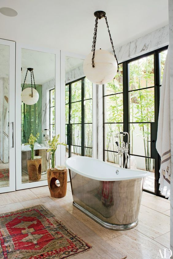 This Designer bathroom has it's own personality..elegant and on point.  Via   Similar bath tub  here  and  here . Persian Rug  here