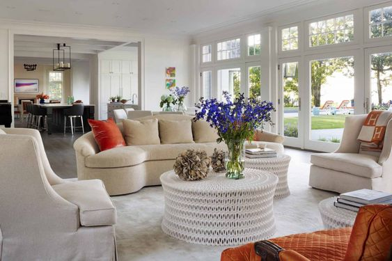 The interior is vibrant and fresh with modern artwork on the walls, a neutral color palette with a pretty shade of orange accent pieces that brighten the living area.