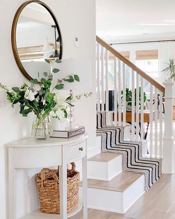 This entry way is so fresh and pretty, and a beautiful way to welcome your guests to your home.   Via     shop striped stair runner.. here  and  here . shop round mirror..  here   and   here  . This pretty white console table is available   here  . I love this classic glass table lamp, available   here   .