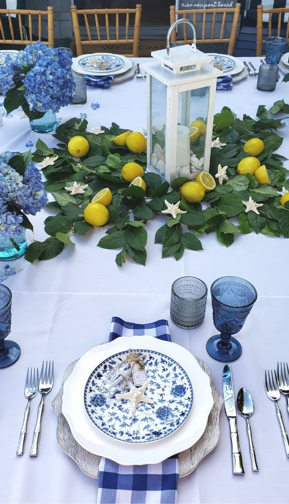 Add a little coastal flair by scattering white starfish around the table on a bed of ivy and white lanterns showcasing the centerpiece, then add pops of color to table with fresh lemons-which your guests can you use if serving seafood, and the individual posies filled with light blue hydrangea complete this pretty table.  Ciao!Newport Beach .