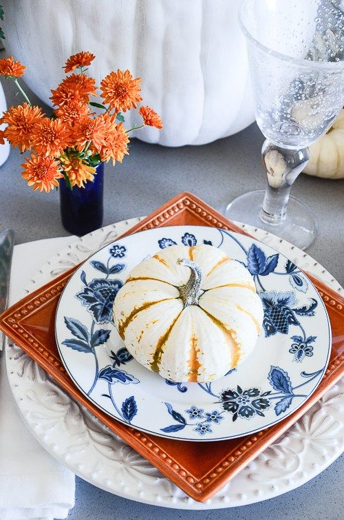 This autumn blue + white tablescape is created by the  Stone Gable  blog. I love how they added a pop of fall color to the place setting, don't you? Layer a spice paprika, golden yellow or bright cranberry charger plate, salad plate or soup bowl.