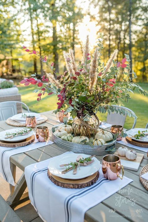 This fall farmhouse Autumn table is so inviting, created by the blogger  Homestoriesatoz  . Showcasing the natural elements of Fall with the natural wood charger plates, baby pumpkins and a centerpiece filled with a bounty of natural yard clippings.