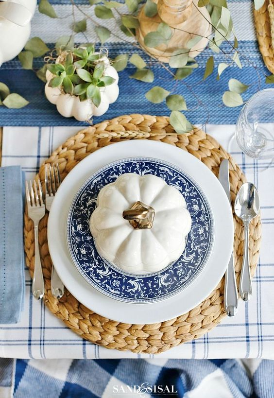 Create a beautiful blue + white Autumn table by layering a blue table cloth and adding a white + blue stripe place mat, and sold blue napkin. Tablescape by the blogger  Sand & Sisal . How pretty are the individual soup terrains?