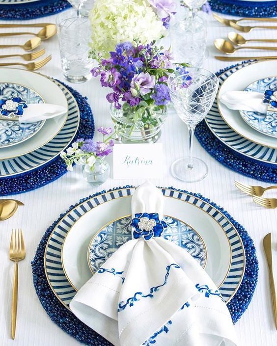 A sophisticated blue and white table palette. Gold rimmed dinner plates and flatware add a touch of regal luxury-and the blue and white linen napkins and jewel napkin ring almost makes this dinner setting too flawless to use.  Via