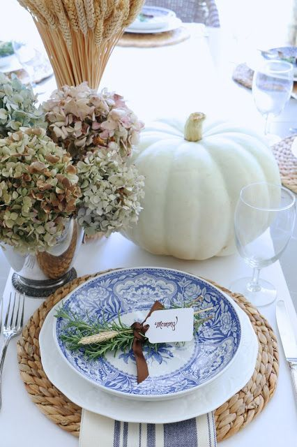 This tablescape is created by the  Eleven Gables Blog , how simple and pretty is the fall centerpiece of hydrangeas, white pumpkins and a vase filled with a bundle of wheat stems. A crisp and white table runner, showcases the water hyacinth round placemat and the gorgeous blue and white dinnerware. I love the pretty herb + wheat posy place card.