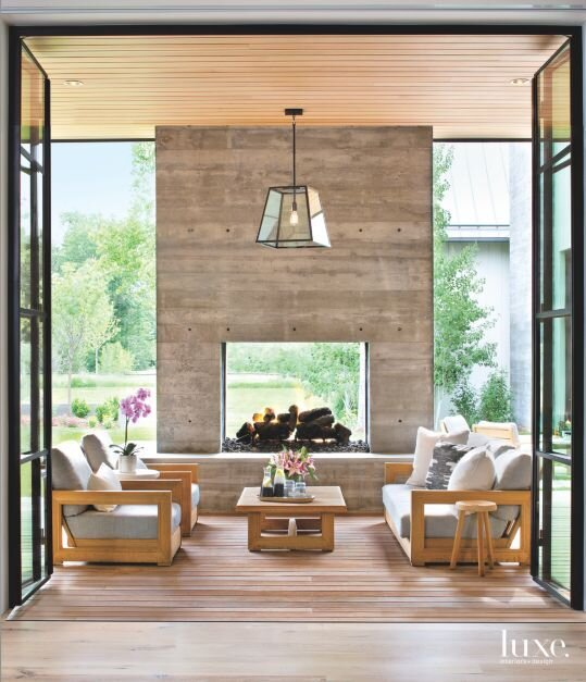 Steel-and-glass doors open to the glamorous sunroom. A showstopping floor to ceiling board-form concrete fireplace gives you a peak a through view of the landscape. Beautifully furnished with contemporary teak furniture. Designed by interior designer Alvarez Morris.