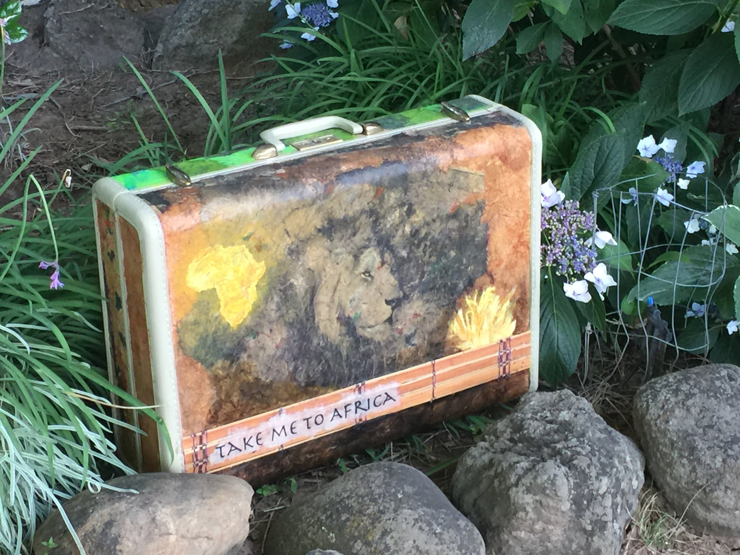 "Using images from past African safaris, I applied acrylic glazing mediums to adhere some of my rice-paper printed images to the exterior of this vintage suitcase. Then... on the inside I added more color and vibrance with a silkscreen I made of an African Acacia tree with a zebra. I also had a piece of plexiglass cut to fit, which I painted to resemble a watering hole, so that it could provide a ""stage"" of sorts for a traveling safari. Beneath the plexiglass are a myriad of African animals nestled inside colorful canvas bags ready to get out and play...  Another piece of my  breaking out series  of art created beyond my comfort zone."