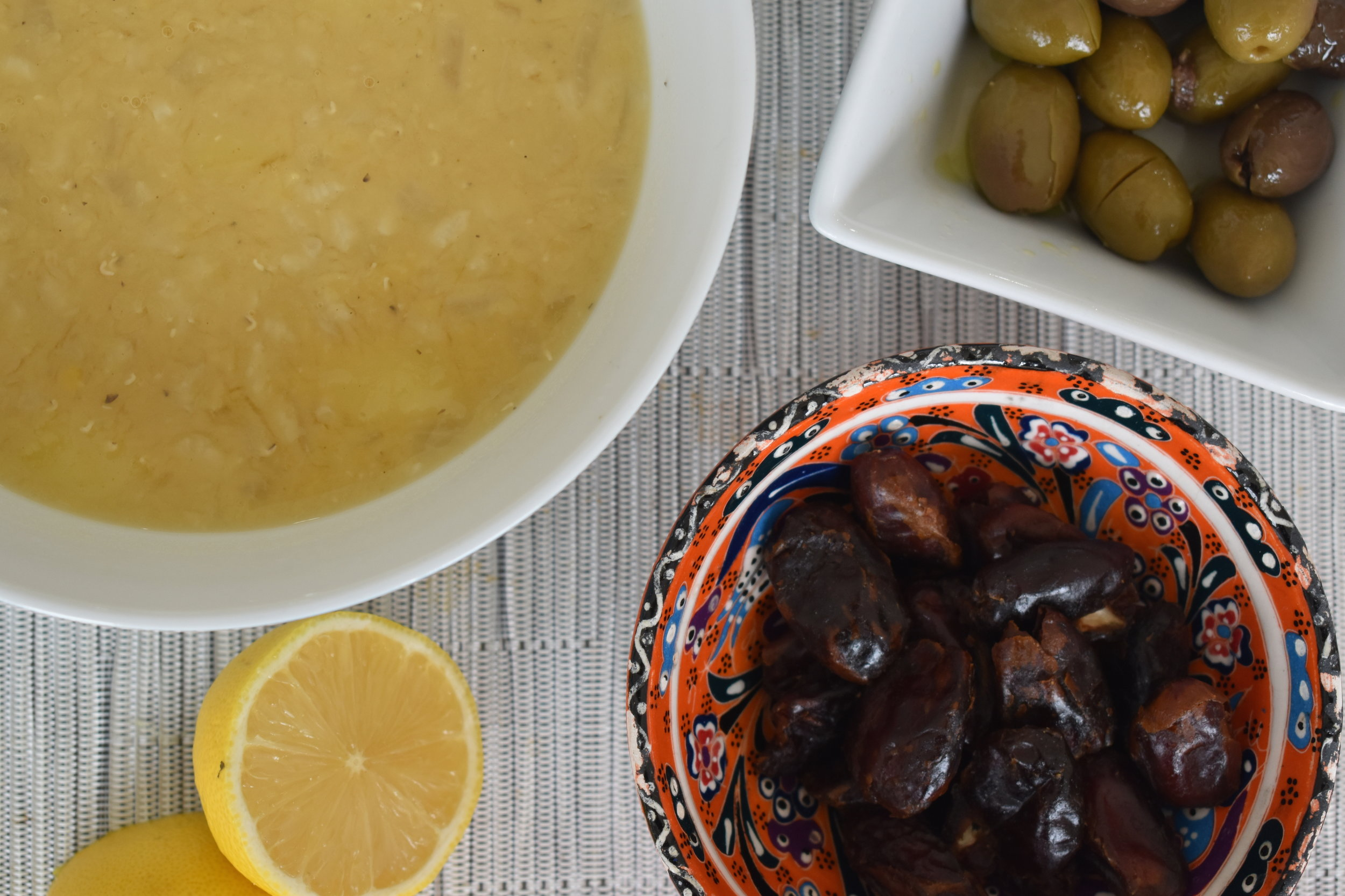Red Lentil Soup served with lemon and sides of olives and dates