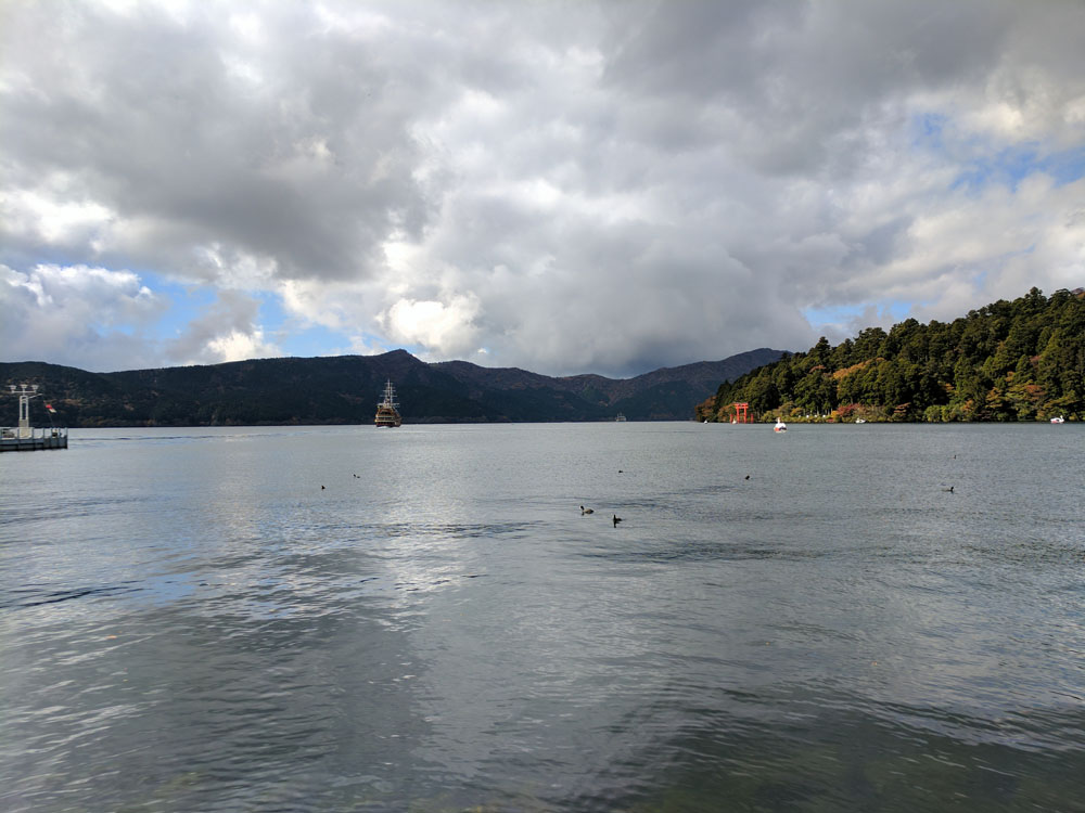 Looking out over Lake Ashinoko with the Hakone Shrine torii gate and Mt. Fuji hidden behind clouds