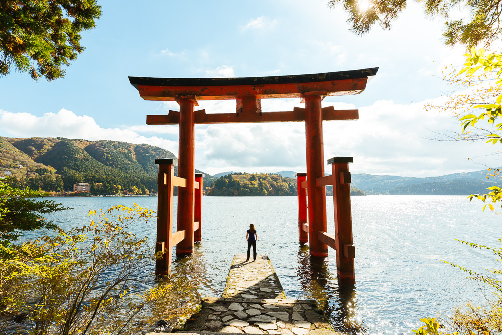 Standing under the Hakone Shrine torii gate which sites at the waterfront of Lake Ashinoko