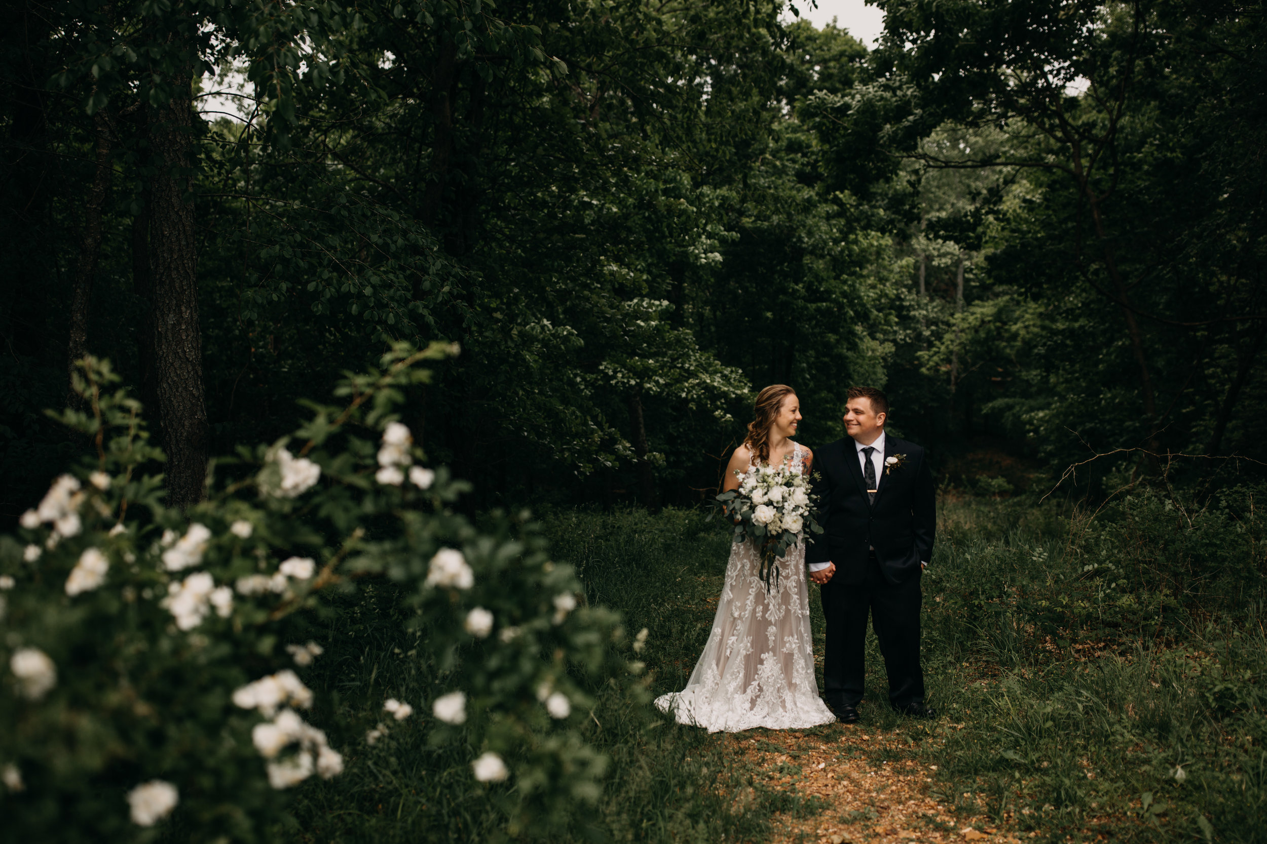 bride and groom in forest looking at each other