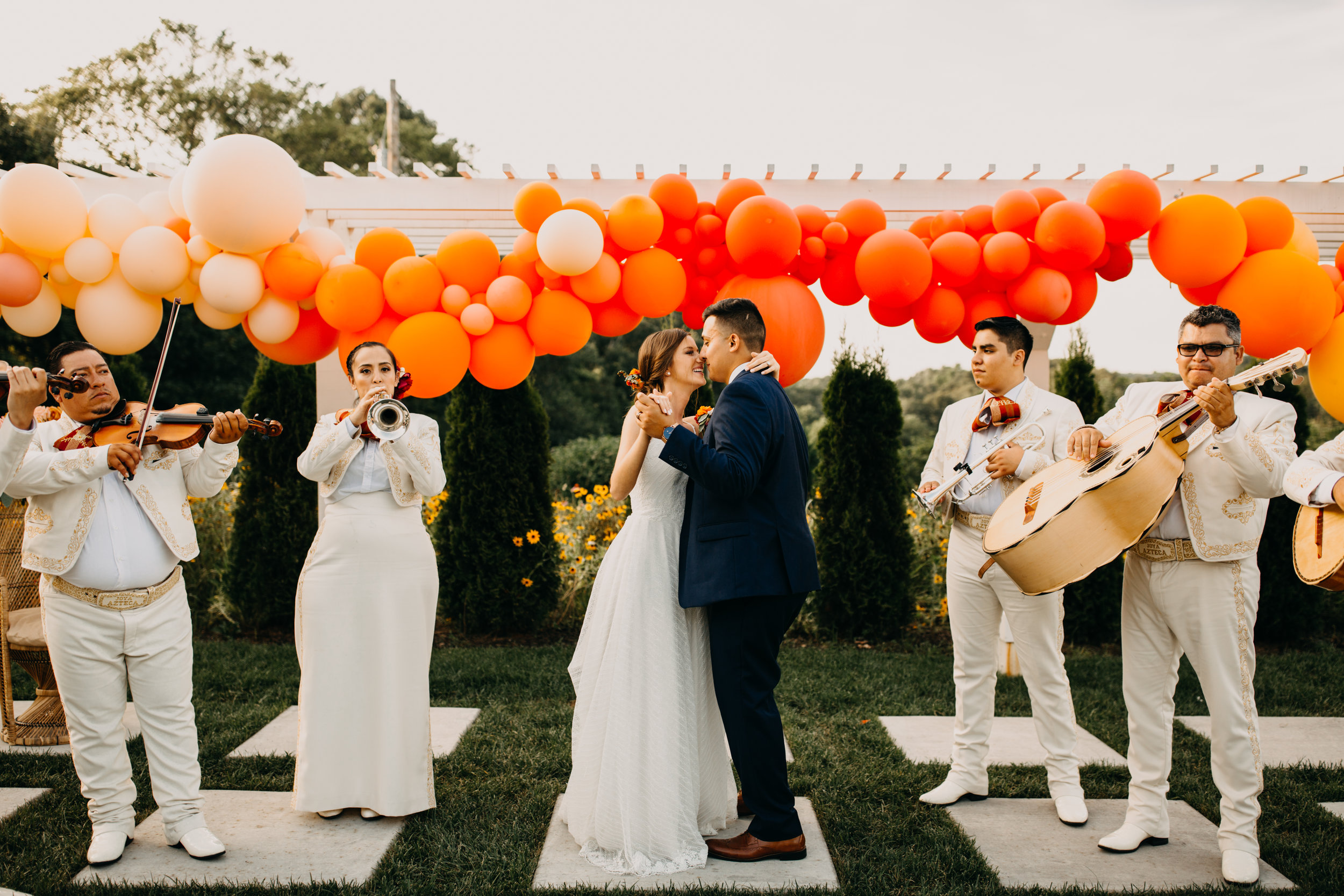 bride and groom in front of balloons and mariachi band