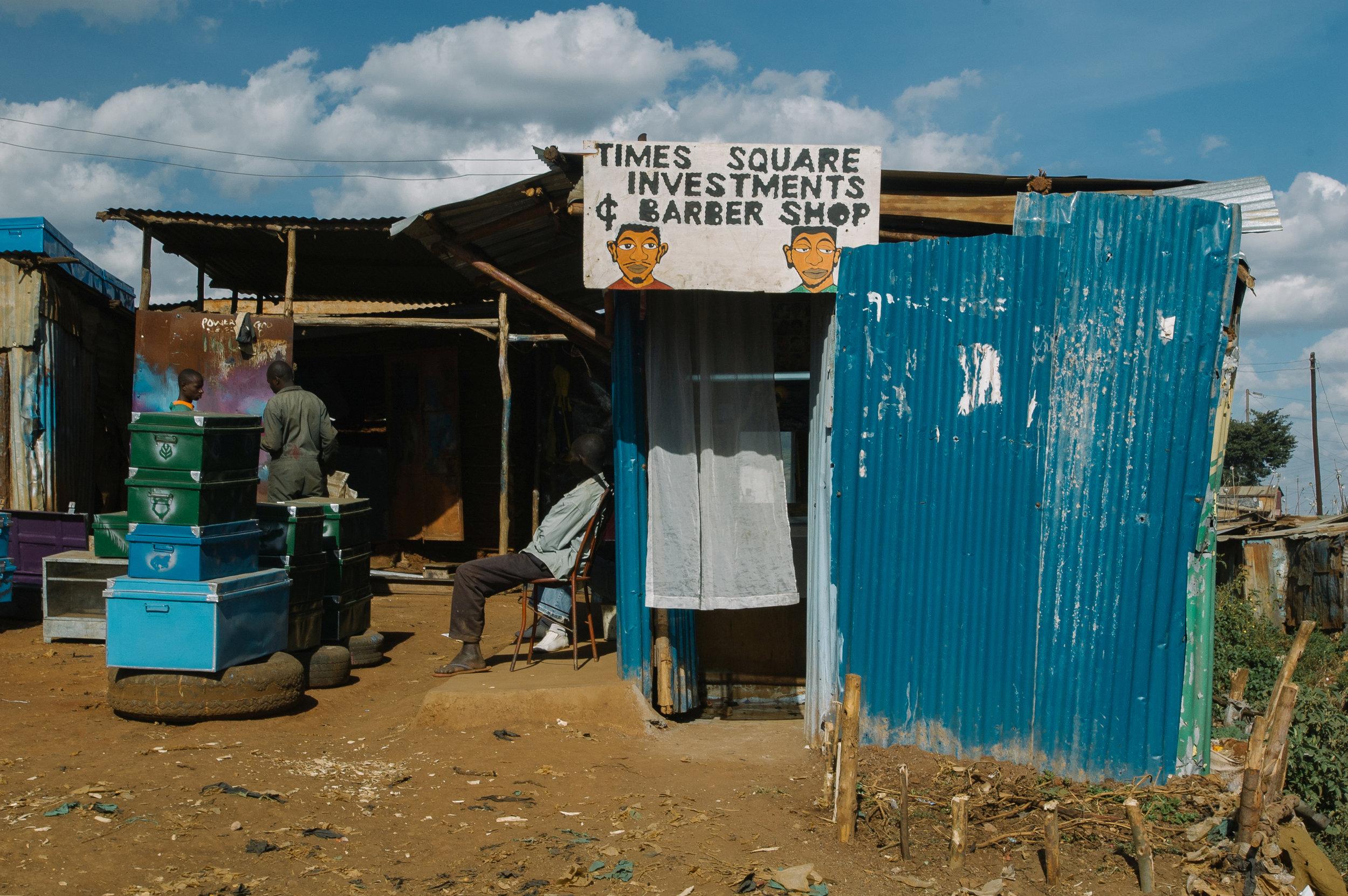 Kenianer warten vor einem Friseur.